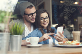 Embracing couple using mobile phone in cafe